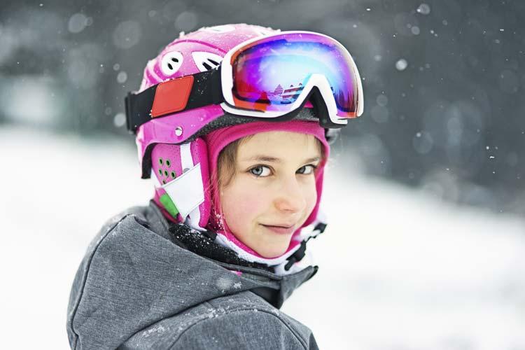 Bambina nella neve con casco da sci