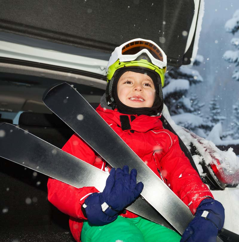 Boy with ski equipment on chair lift